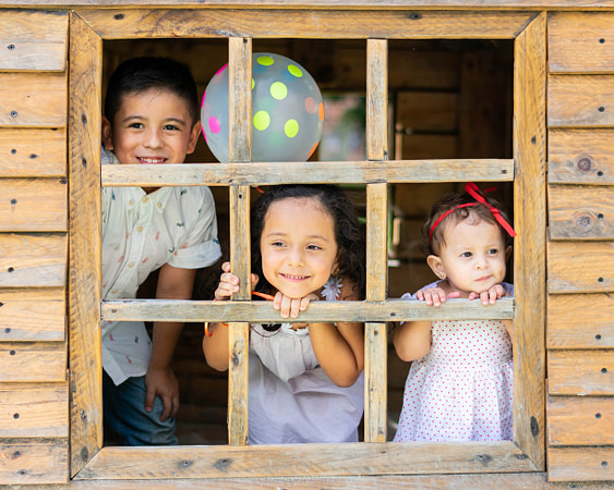 Three young children that are siblings smiling and looking out the window of a playhouse for psychology resources blog post that has helpful tips and content.